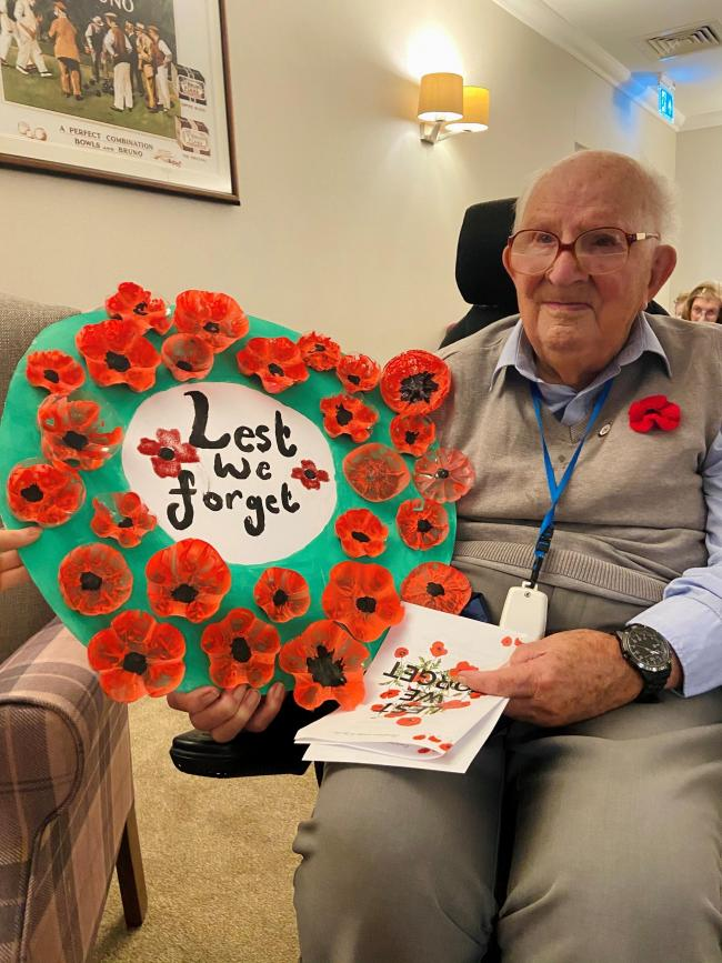 Geoffrey Scovell lays his crafted poppy wreath