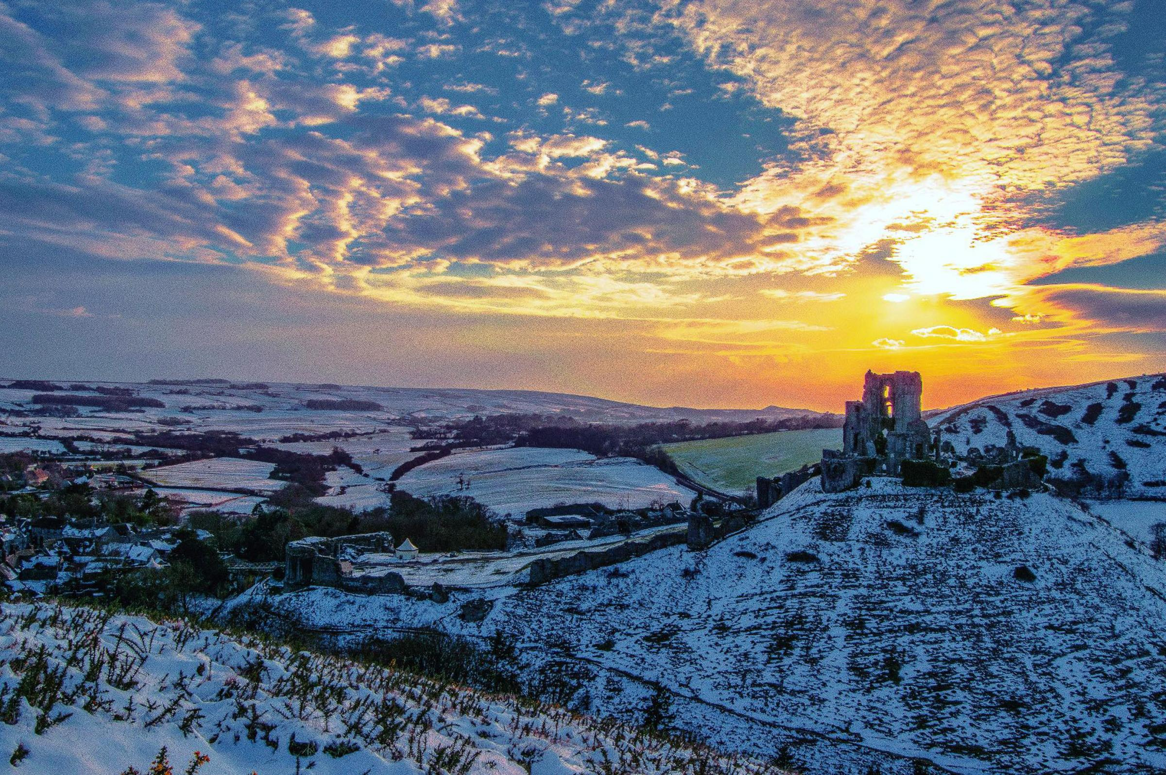 The sun sets over a snow covered Corfe Castle in Purbeck taken by Echo Camera Club member Joanna Louise