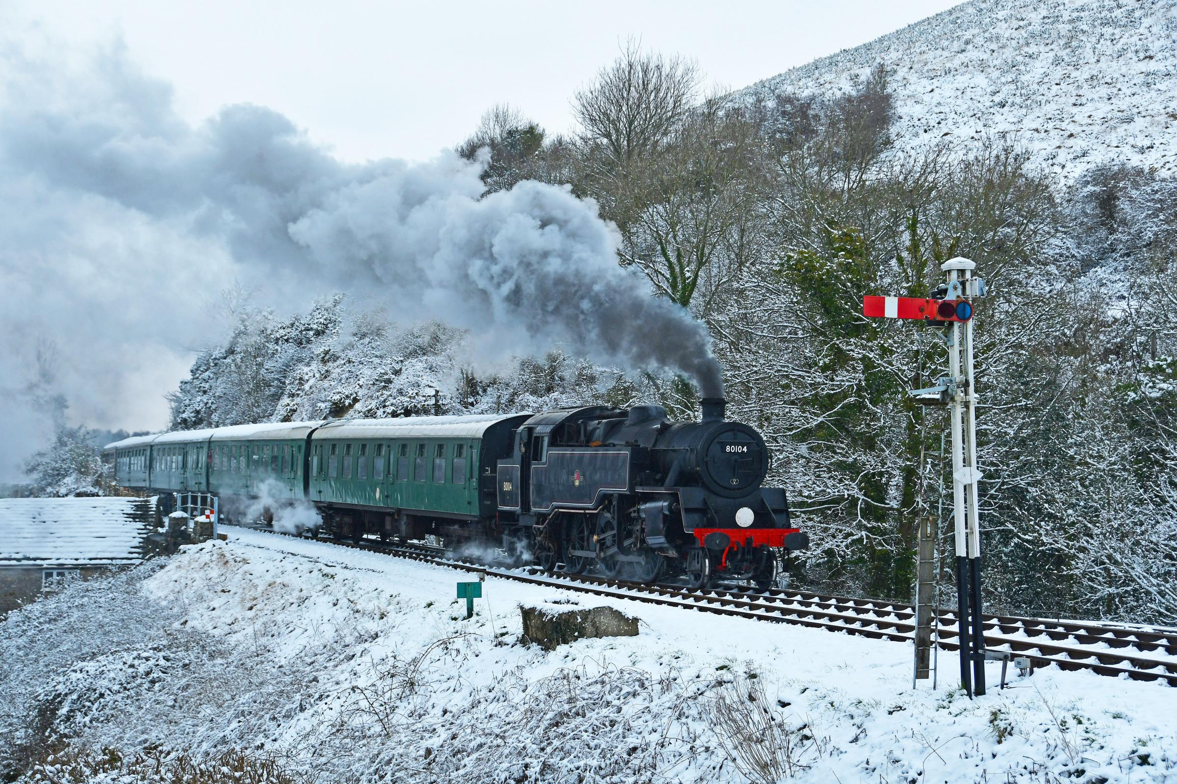Swanage Railway's 80104 train steaming into Corfe Castle below a snow covered Challow Hill taken by David Watson.