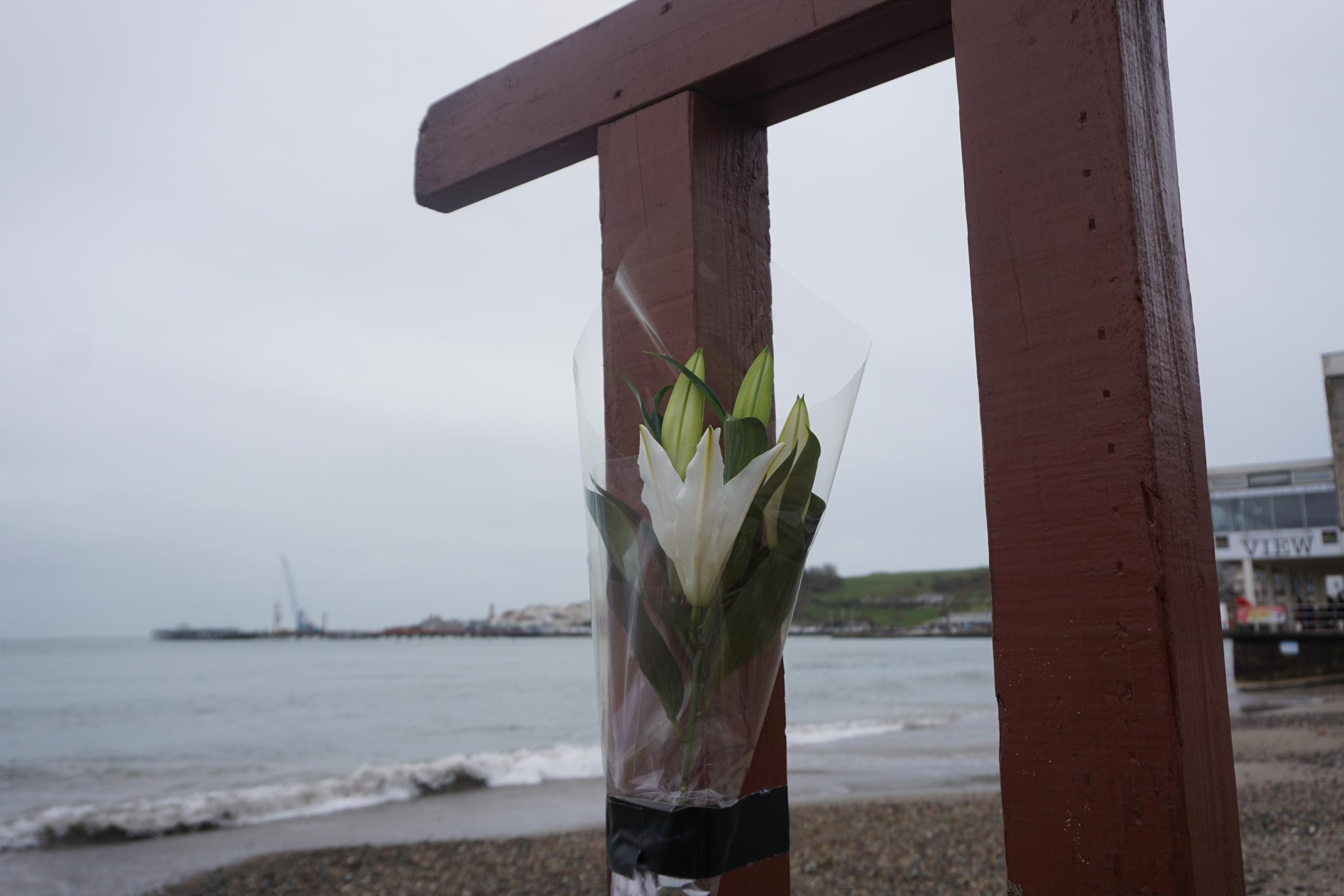 Flowers left at the scene where a man died after being hit by a car on Swanage seafront on Monday